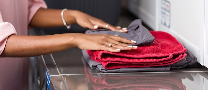 woman-folding-red-towels